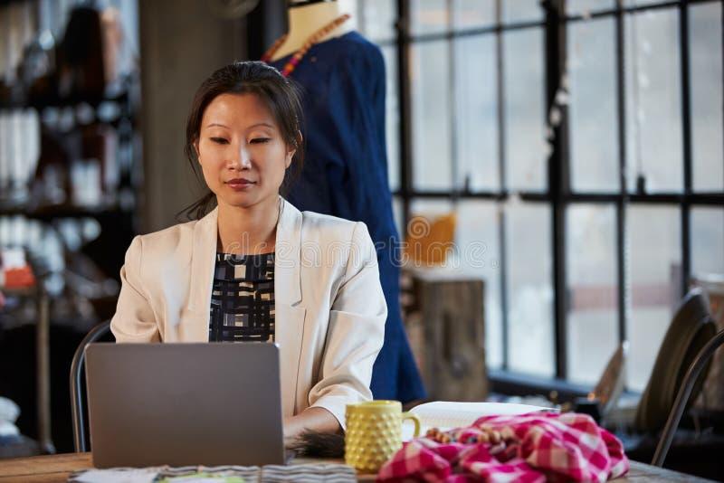 Couturier féminin Working At Laptop dans le studio photo libre de droits