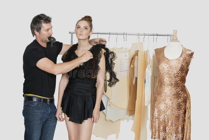 Couturier masculin mûr ajustant la robe sur le modèle dans le studio de conception photos stock