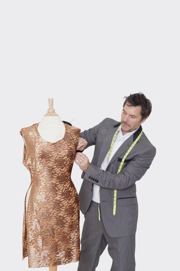 Couturier masculin mûr ajustant le tissu sur le simulacre du tailleur au-dessus du fond gris images stock