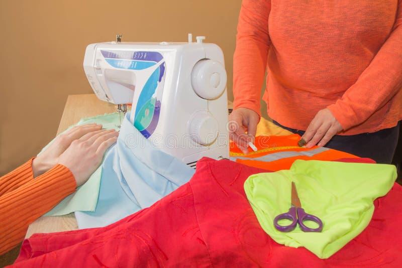 Couturier naait een kleding in de studio Manierontwerper die een patroon op een rood stuk van weefsel maken stock afbeelding