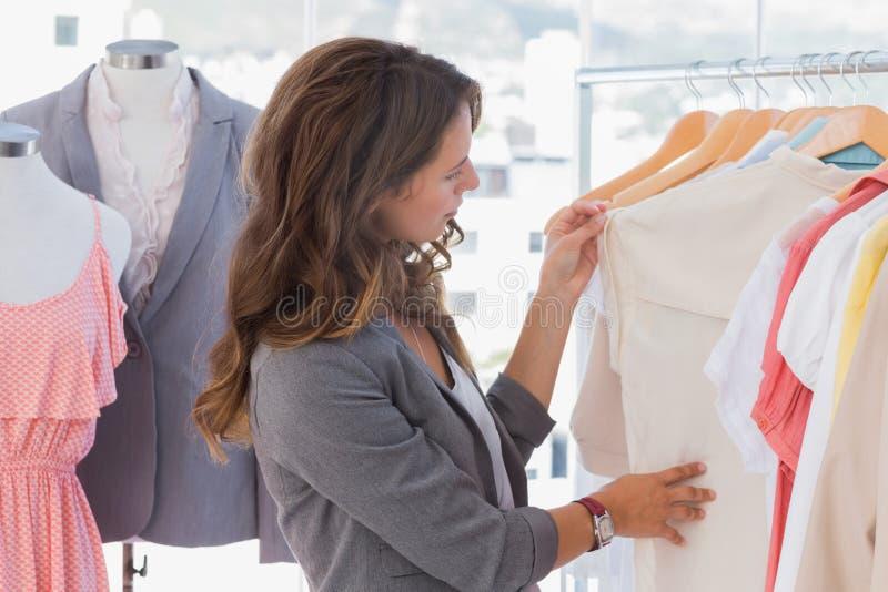 Couturier regardant des vêtements images libres de droits