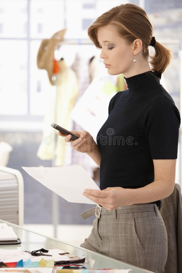 Couturier utilisant le mobile photo stock