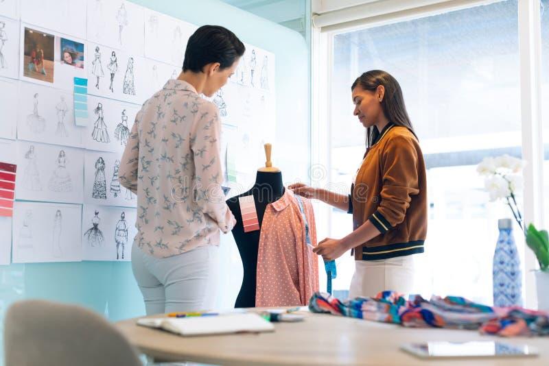 Couturiers féminins travaillant travailler ensemble au vêtement sur le modèle de couturière image libre de droits