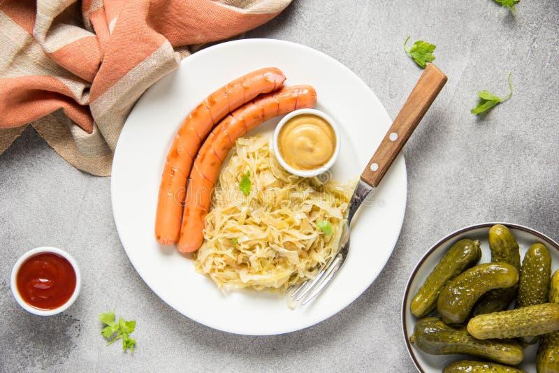 Couve branca assada com as duas salsichas fritadas longas, a mostarda e os pepinos conservados Alimento b?varo h?ngaro alem?o cl? foto de stock