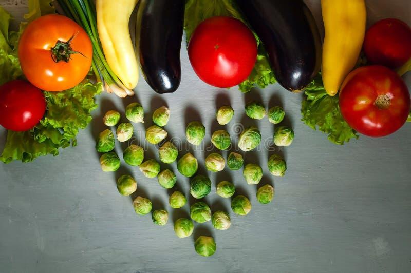 Couve de Briussel na forma do coração e de legumes frescos para o cozimento saudável em um fundo de madeira claro, configuração d imagem de stock
