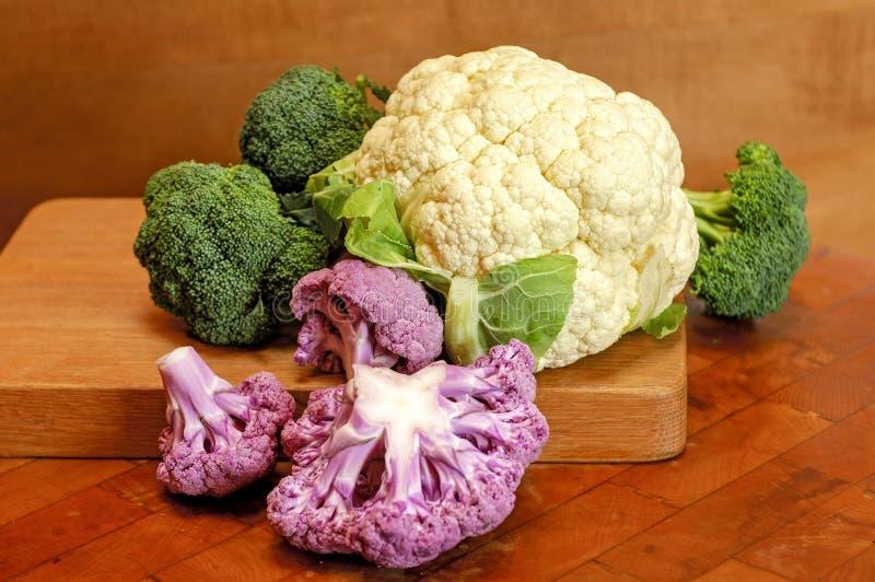 Couve-flor e brócolis coloridos na placa de corte fotos de stock royalty free