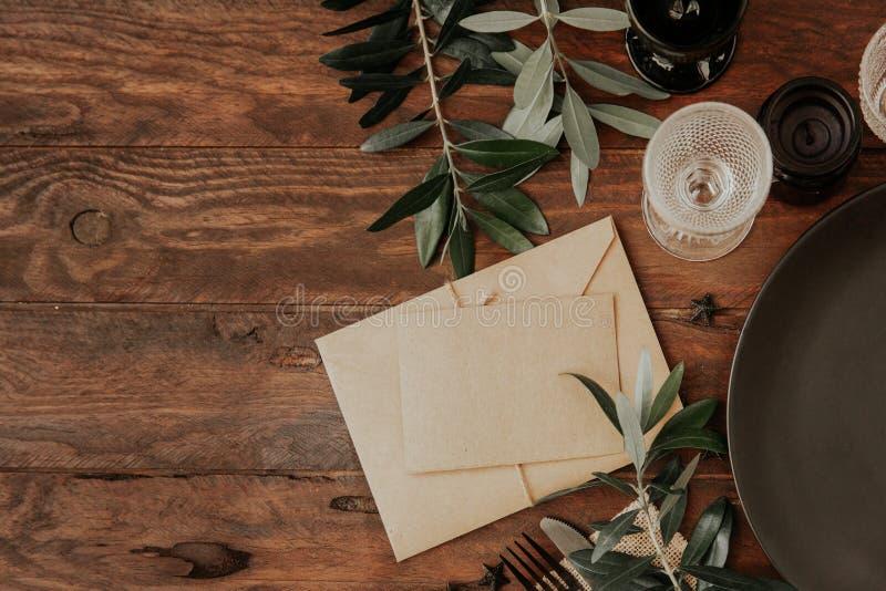 Couvert rustique de table avec la serviette de toile, branche d'olivier sur le fond en bois photo libre de droits