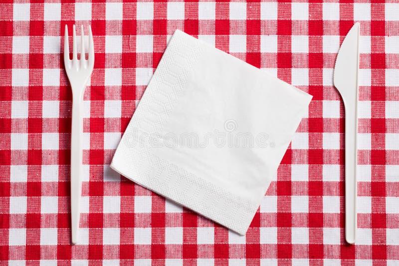 Couverts en plastique sur la nappe checkered photo libre de droits