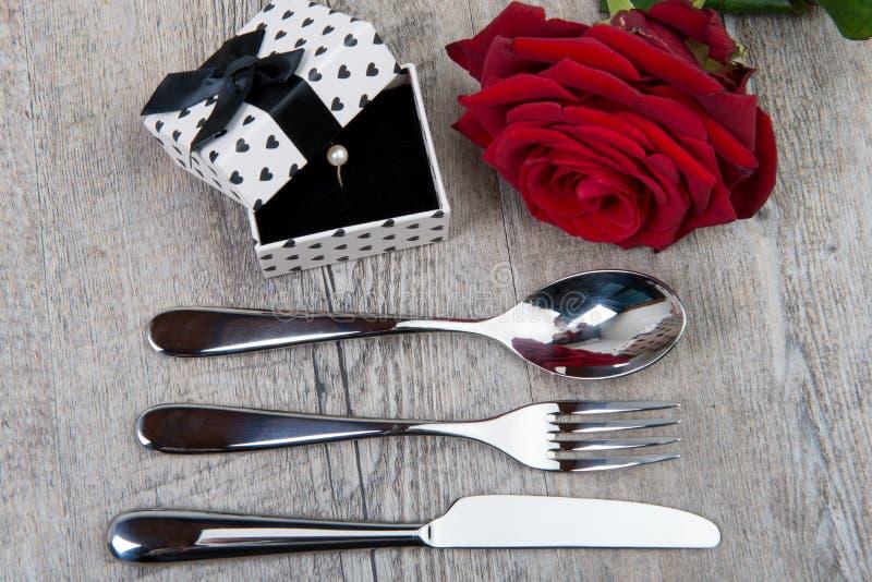 Couverts, rose et cadeau pour la Saint-Valentin image stock