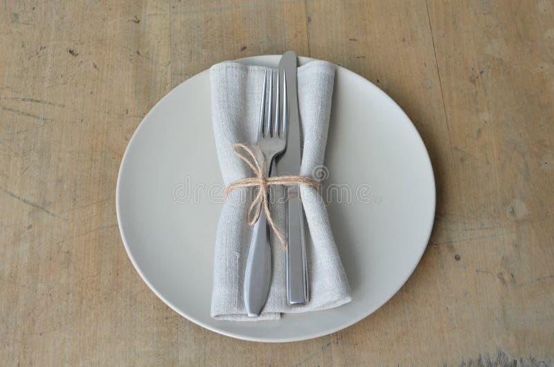 Couverts sur une serviette verte décorée d'une cuvette, un plat tout préparé Sur un conseil en bois photographie stock libre de droits