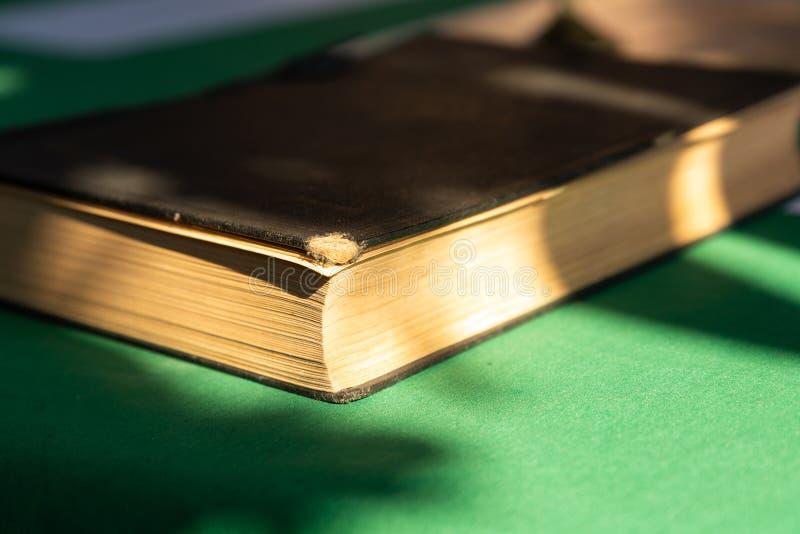 Couverture brune déchirée en lambeaux de vieux livre sur le soleil extérieur de rayons de bibliothèque de tissu vert photo stock