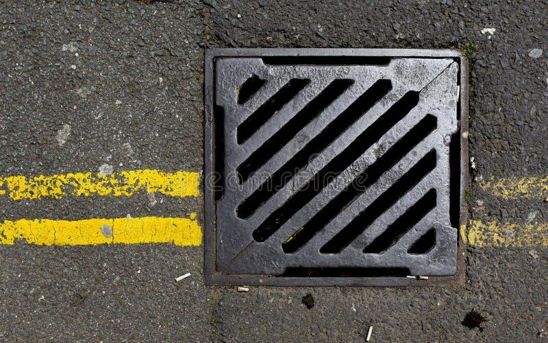 Couverture d'égout avec de doubles lignes jaunes photographie stock