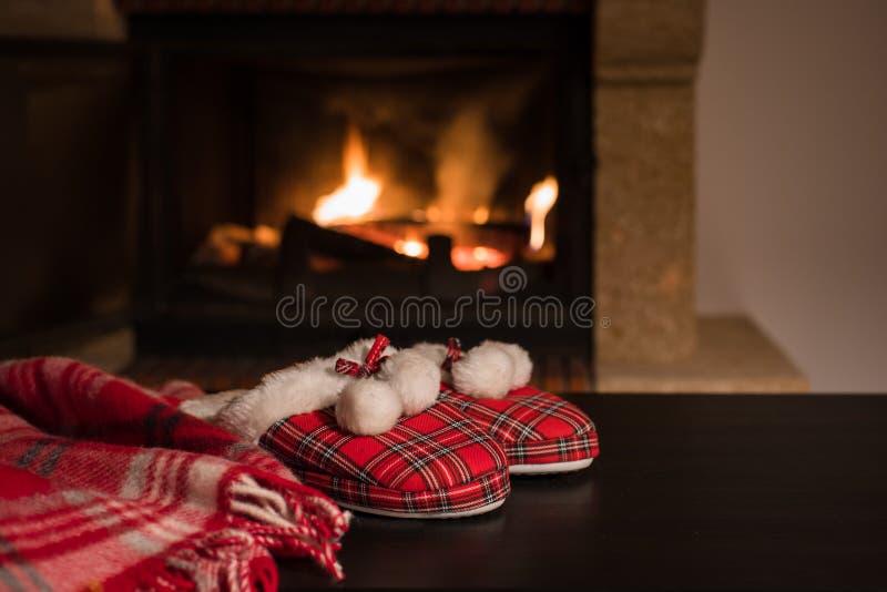 Couverture de laine ou plaid chaud et pantoufles rouges avec des pompons sur le fond de la cheminée brûlante photographie stock