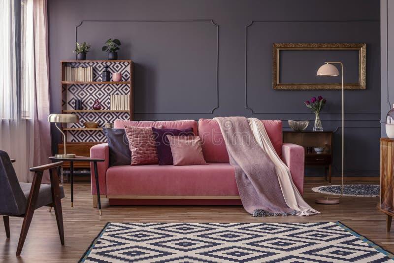 Couverture de rose en pastel sur un sofa assorti dans le salon W intérieur photo libre de droits