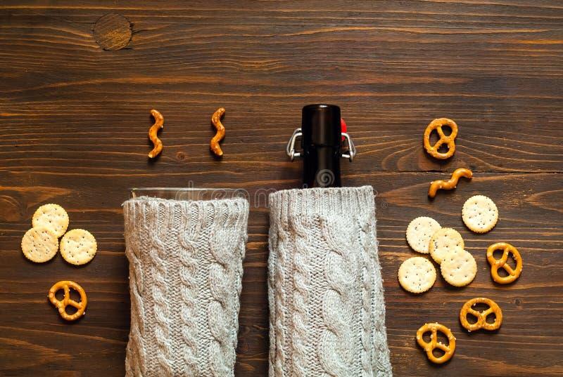 Couverture sur la bouteille de style scandinave sur le fond en bois, concept des accessoires confortables pour des boissons, l'es image libre de droits