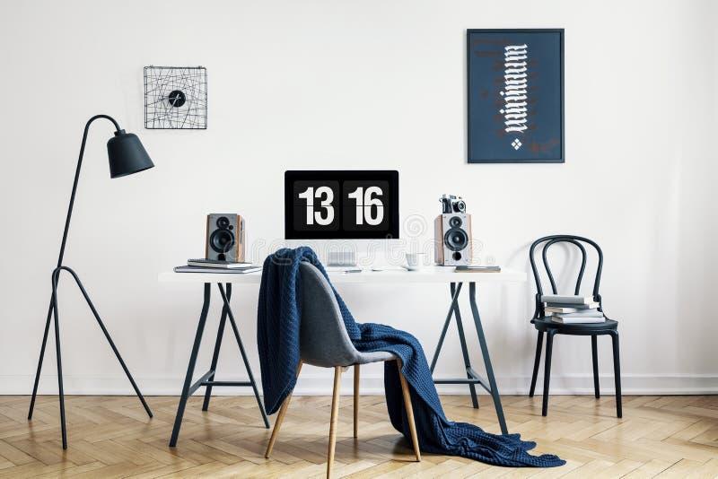 Couverture sur la chaise au bureau avec l'ordinateur de bureau dans l'intérieur d'espace de travail avec les affiches et la lampe photographie stock