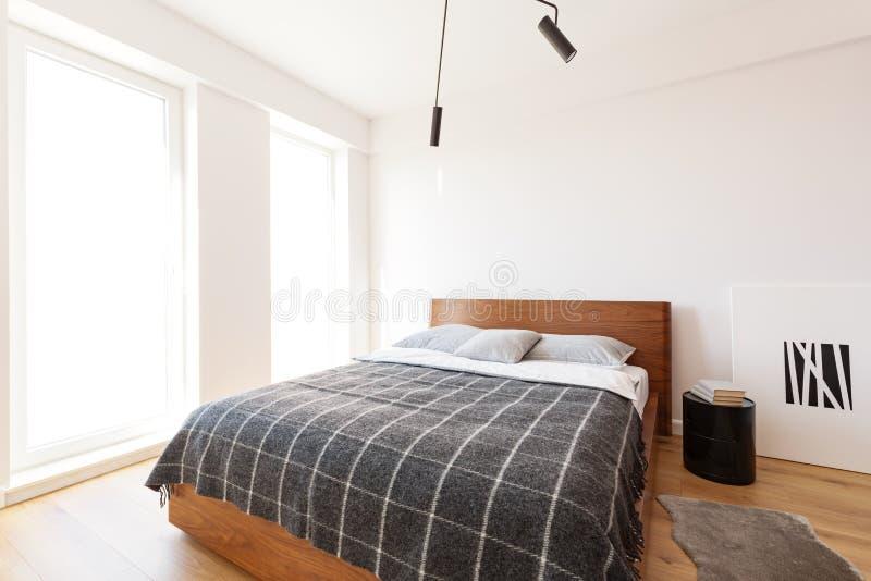 Couvrant modelé sur le lit en bois dans l'intérieur blanc de chambre à coucher avec p photos stock
