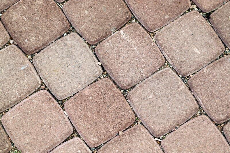 Couvre de tuiles la place rosâtre sous la pierre comme fond photographie stock