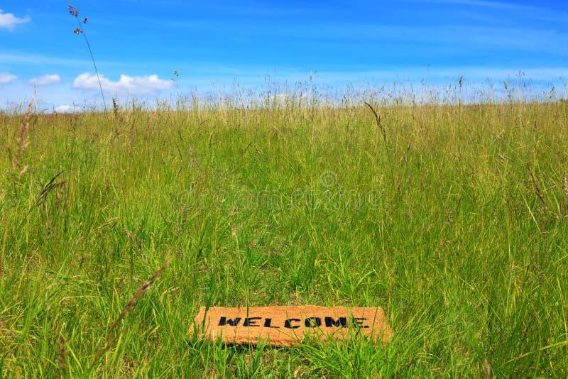 Couvre-tapis bienvenu dans un pré d'herbe avec le ciel bleu images libres de droits