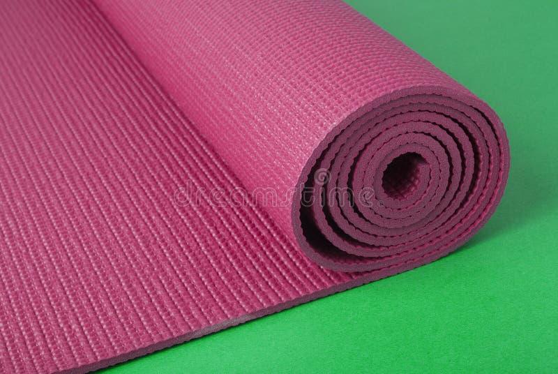 Couvre-tapis rose de yoga sur le vert photo libre de droits