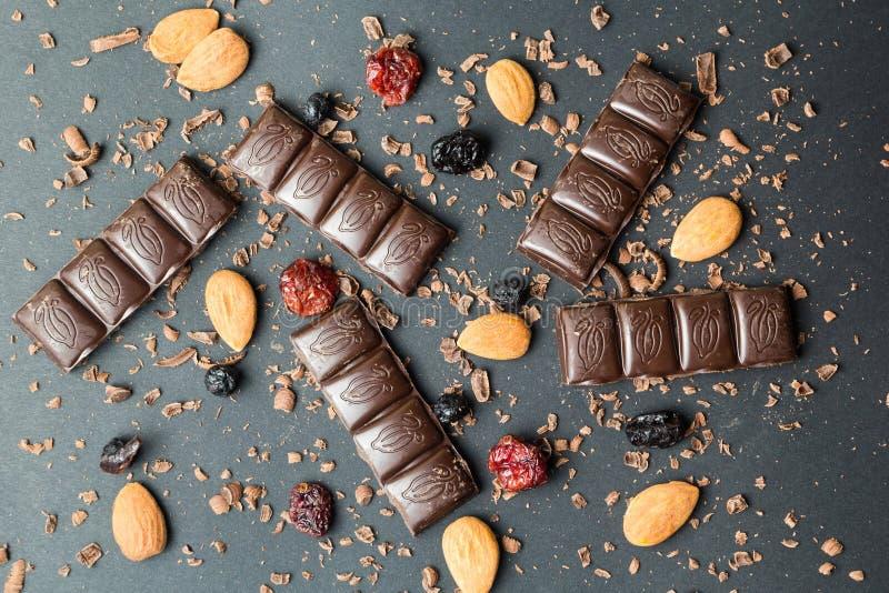 Couvrez de tuiles le chocolat noir avec les fruits secs sur un fond noir, lumière de gradient photographie stock libre de droits