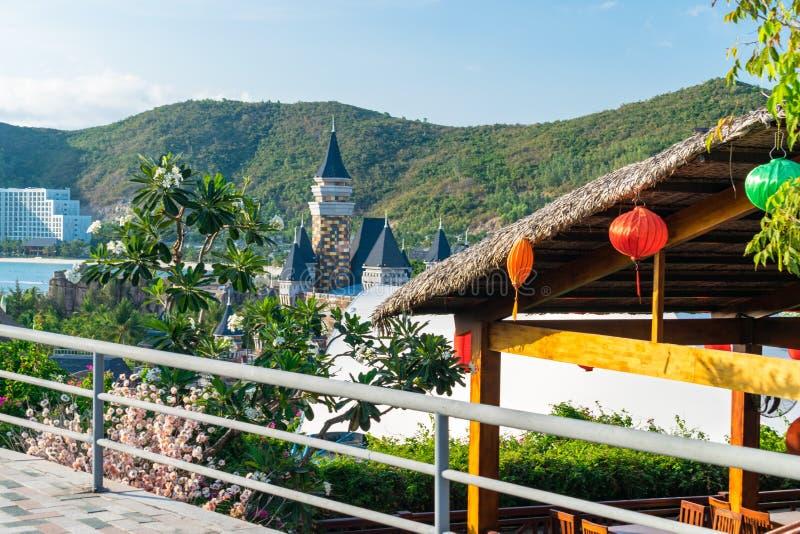 Couvrez le toit de chaume avec les lanternes chinoises colorées avec des fleurs le fond de la colline images stock