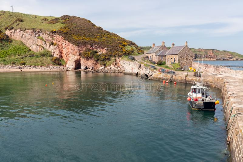 Cove harbor with fishing ship at Scottish North Sea coast. At the quay lobster cages ready to use stock photo