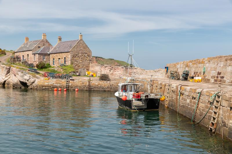 Cove harbor with fishing ship at Scottish North Sea coast. At the quay lobster cages ready to use royalty free stock photo