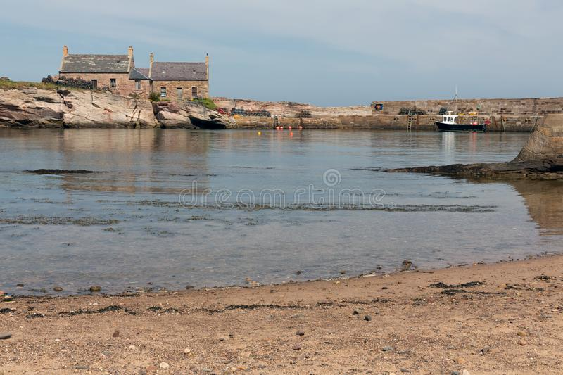 Cove harbor with fishing ship at Scottish North Sea coast. At the quay lobster cages ready to use stock images