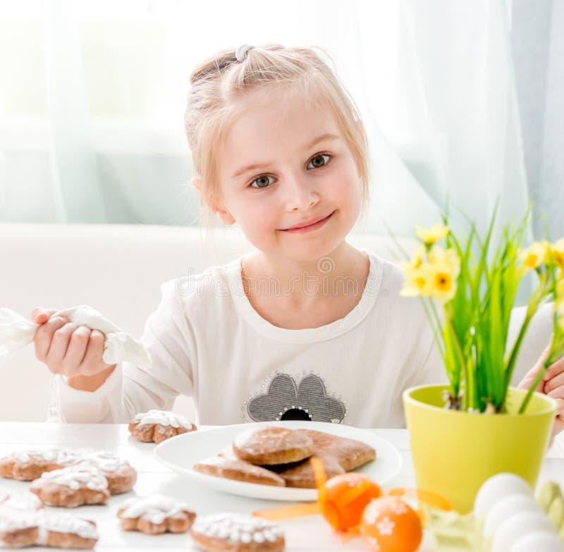 Coveing pepparkaka för liten flicka med isläggning arkivfoto