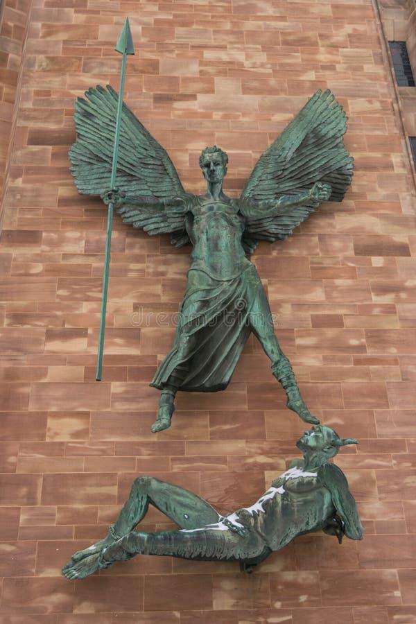 COVENTRY ENGLAND, UK - 3rd mars 2018: St Michael och jäkeln skulpterar vid den berömda konstnären Jacob Epstein på Coventry arkivbild