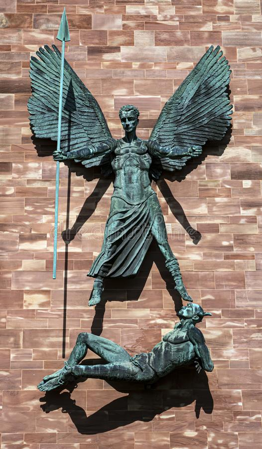 Coventry, UK - August 13 2019: A close-up of the sculpture on the exterior of Coventry Cathedral depicting St. Michaels victory royalty free stock photos
