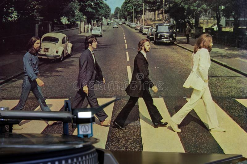 Cover of the famous Beatles Abbey Road album with a turntable in the foreground. royalty free stock image
