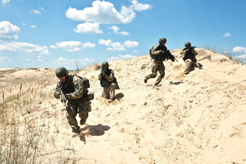 Cover me!. Squad of soldiers run through the desert through the military operation stock photos