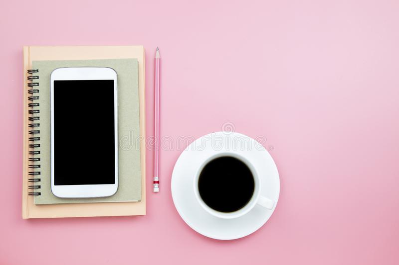 Cover notebook mobile phone pencil black coffee on pink background pastel style with copyspace flatlay topview. Cover notebook mobile phone pencil black coffee royalty free stock photography
