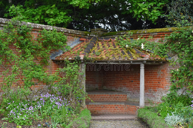 Covered Alcove Seat in Walled Garden at Mottisfont Abbey, Hampshire, England. Mottisfont Abbey was founded as an Augustinian priory in 1201. Mottisfont is now stock image