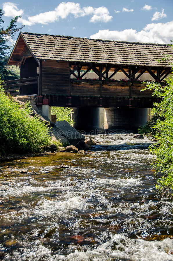 Covered bridge in the Colorado Rocky Mountains with flowing stream royalty free stock photos