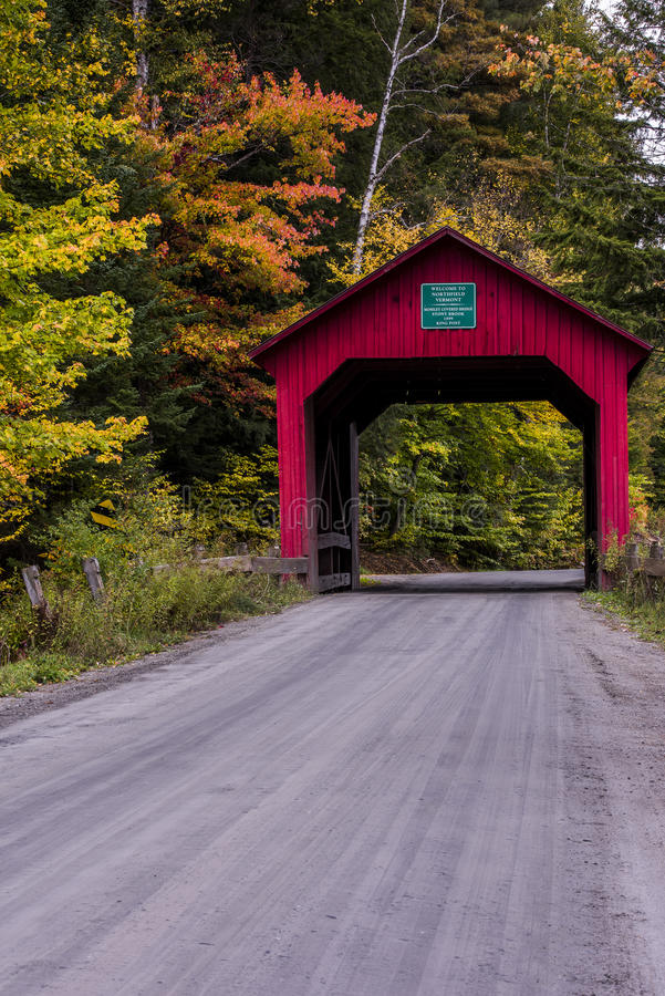 Covered Bridge and Gravel Road - Autumn / Fall - Vermont. A gravel road leads to a historic red painted covered bridge during a beautiful fall / autumn day in royalty free stock photography