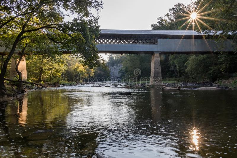 Covered bridge with sunstar and cliff royalty free stock images