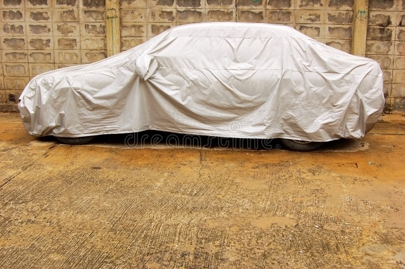 Covered car. A parked car with protective cover in wet weather royalty free stock photos