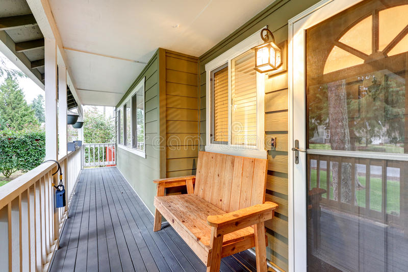 Covered front porch with wood bench next to entrance door royalty free stock photo