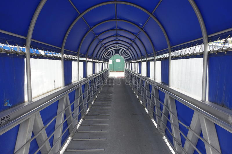 A covered gangway leading to boats royalty free stock images