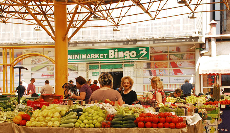 Covered Market in Sarajevo. Sarajevo, Bosnia and Herzegovina - August 10th 2014. A stall holder serves customers at the covered market in Mula Mustafe Baseskije stock photography