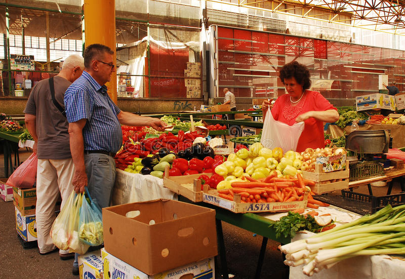 Covered Market in Sarajevo. Sarajevo, Bosnia and Herzegovina - August 10th 2014. A stall holder serves customers at the covered market in Mula Mustafe Baseskije royalty free stock images