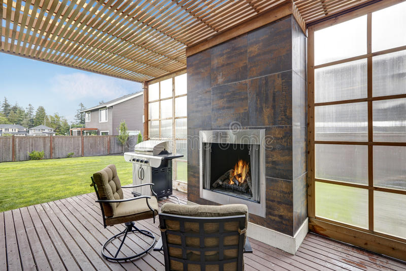 Covered patio area in luxurious house. There is fireplace with brown tile trim, chairs with cushions and barbecue. Northwest, USA stock photo