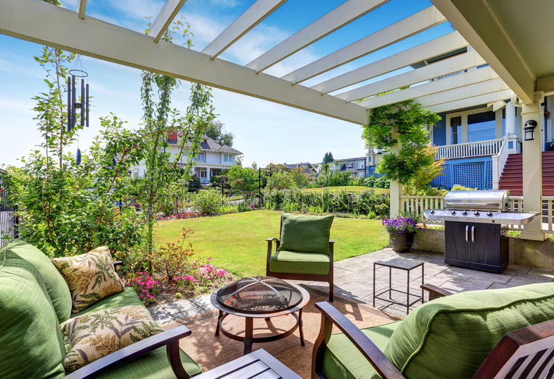 Covered patio area with outside chairs in the backyard garden. House exterior. Northwest, USA royalty free stock image