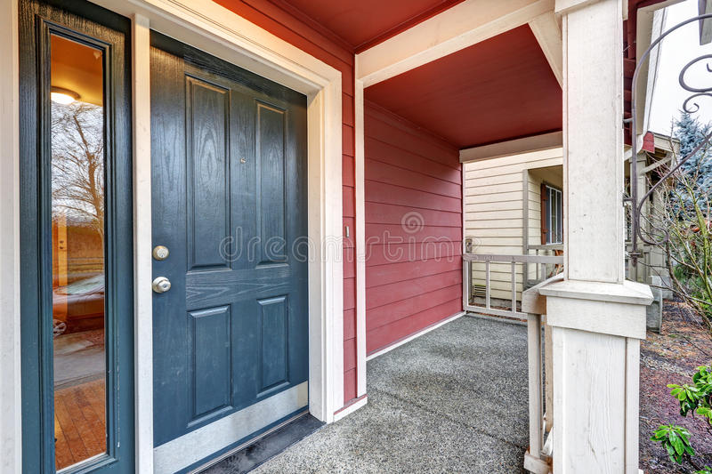 Covered red porch with dark blue accent front door royalty free stock images