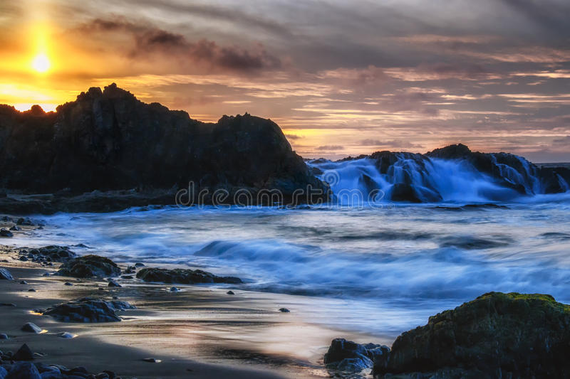 Covered at Sunset. Waves crashing over the rocky shoreline at McClure`s Beach just before sunset royalty free stock photography
