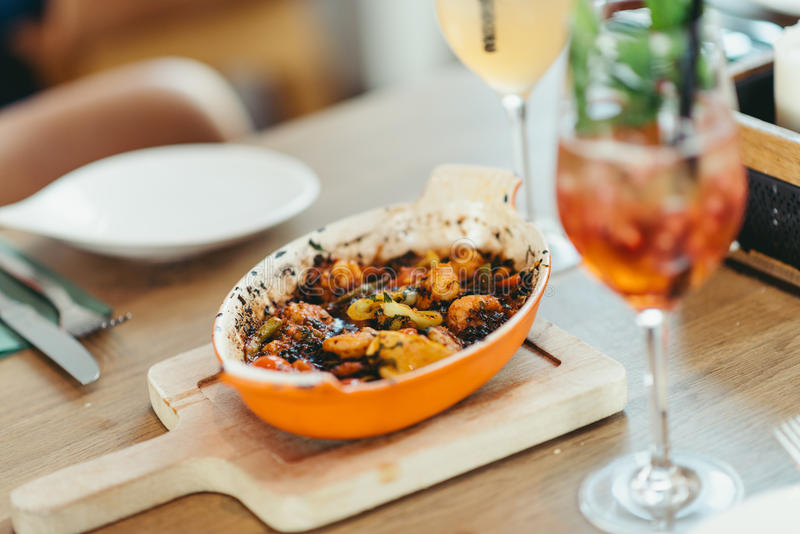 Covered Turkish restaurant table with a shrimp and veggies casserole. And cocktail stock photography