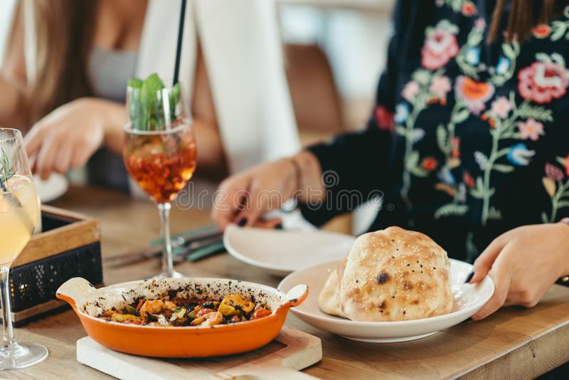 Covered Turkish restaurant table with a shrimp and veggies casserole. And cocktail stock image